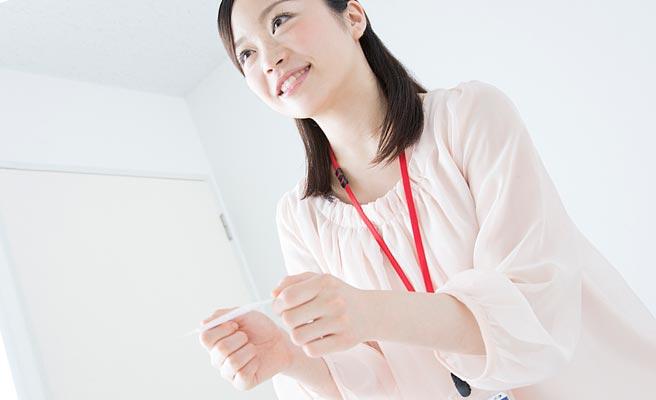 両手で名刺を渡す女性