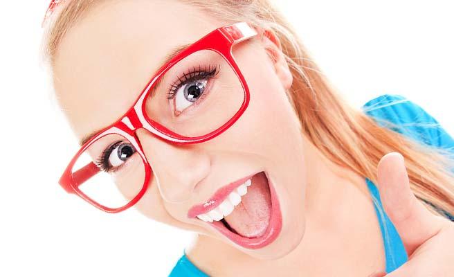 派手な眼鏡をして大きな口を開いてOKサインを出す女性