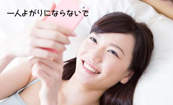 ベッドに横になりながらスマホを見つめる女性