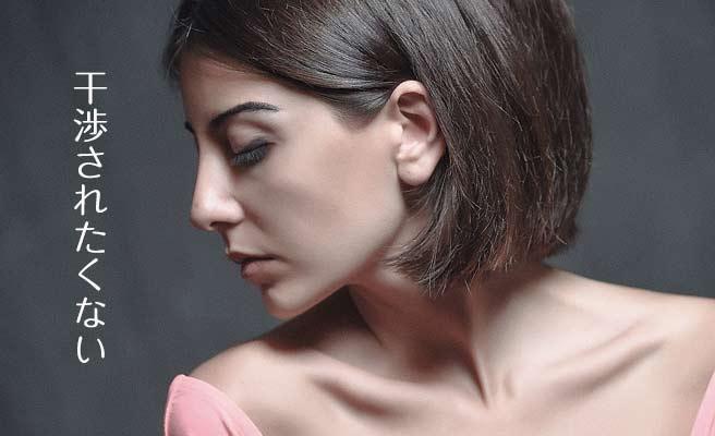 無表情に横を向いて目を閉じる女性