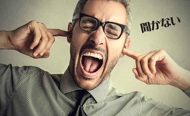 耳を塞いで話を聞かない男性