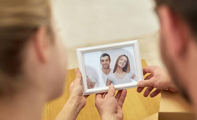 額縁に入った思い出の写真を見るカップル