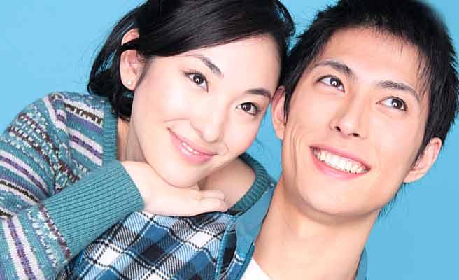 彼氏の肩に手をかけて微笑む女性