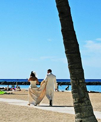 ハワイの海岸通りを歩く新郎新婦