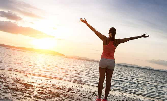海に向かって一人両手を広げる女性