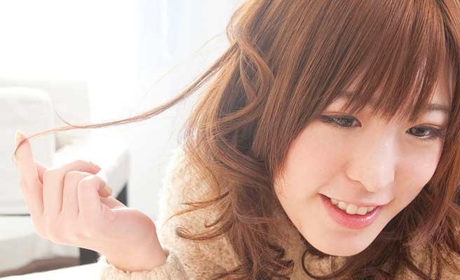 指で髪の毛をいじる女性