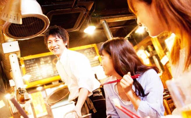 男性ホールスタッフの顔を笑顔で見ている女性