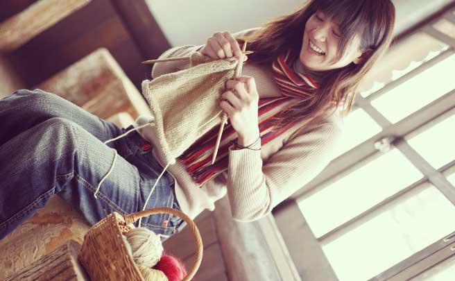 彼氏のプレゼントの為にマフラーを編んでる女性