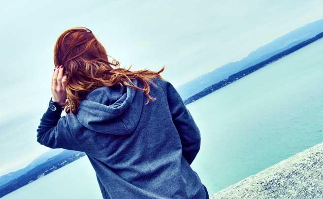 海を見ているパーカーを着た女性
