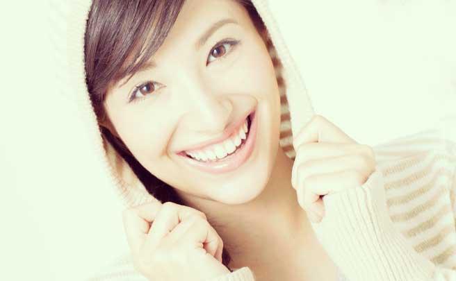 部屋着っぽいパーカーを着てる笑顔の女性