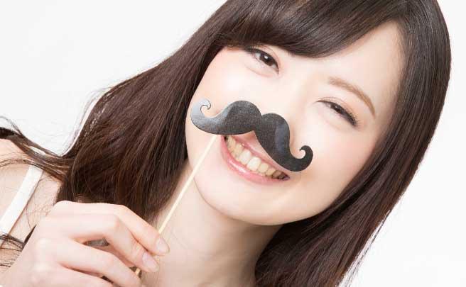 髭のフォトプロップを付けて笑顔の女性