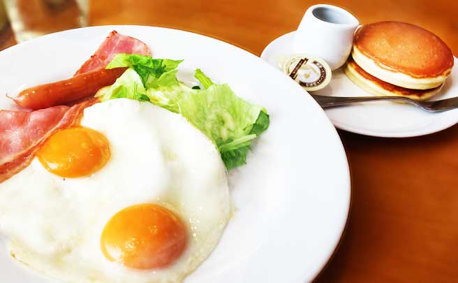 ベーコンとウインナーが添えられた目玉焼きの朝食