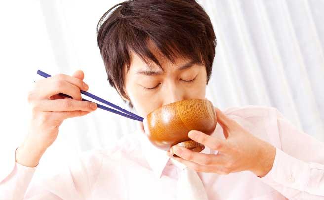 味噌汁を飲んでいる男性