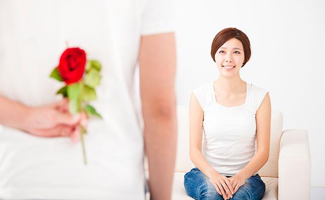 彼女にバラをプレゼントする男性