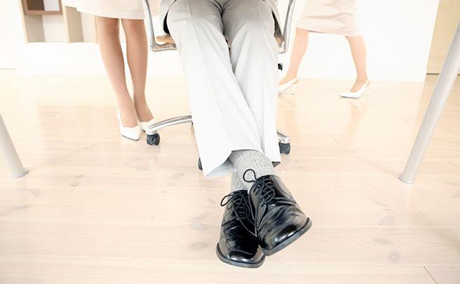 足を組んで座っている男の人の足