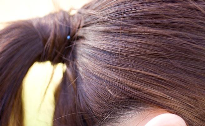 髪留めゴムで髪をアップにまとめている女性