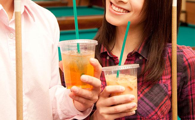 ビリヤードをしながらアイスコーヒーを飲むカップル