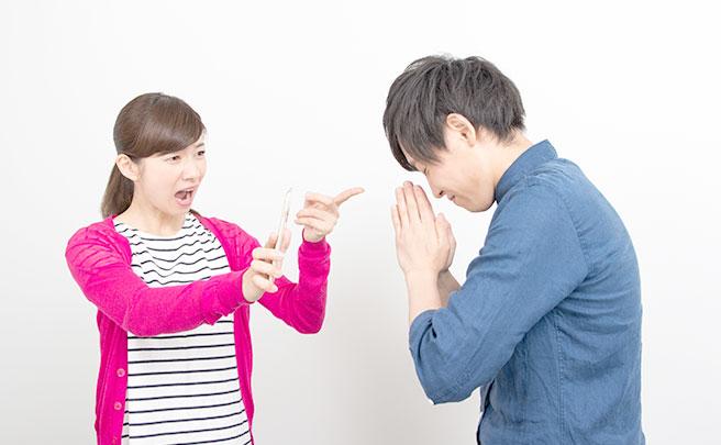 スマホを手に浮気を問い詰める彼女に手を合わせて謝る彼氏