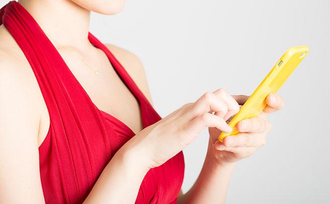 黄色いスマホを操作する赤いドレスを着る女性