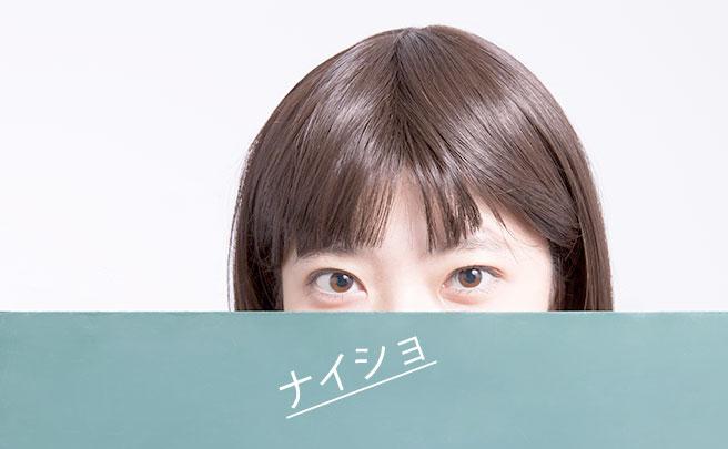 黒板の後ろに隠れる女性