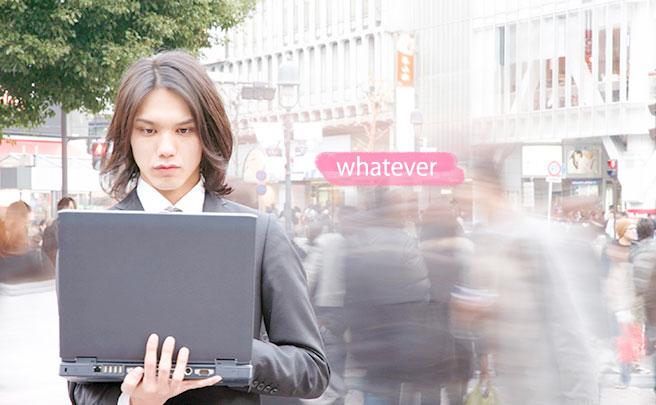 町中で歩きながらノートパソコンを操作する男性