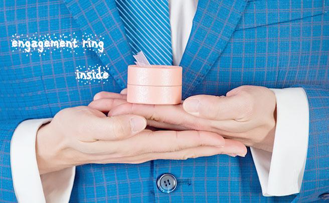 小さいピンクの箱を持つ男の手