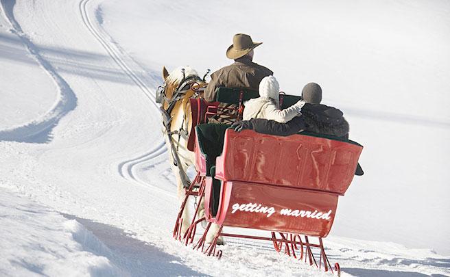 海外で雪の中で馬ソリに乗るカップル