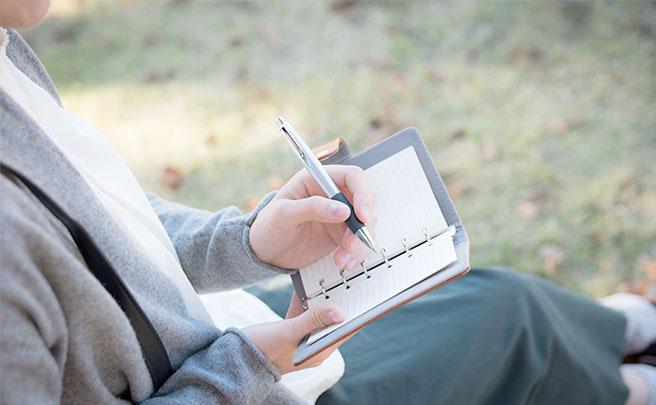手帳にメモをしてる左利きの男性