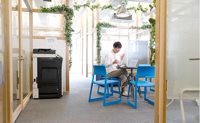 会社の休憩スペースで1人スマホを見る男性