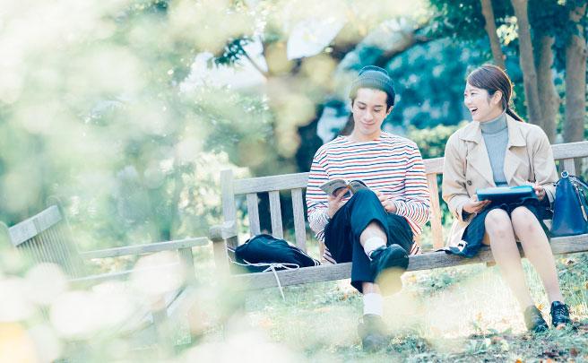 ベンチに座って笑顔で話してるカップル