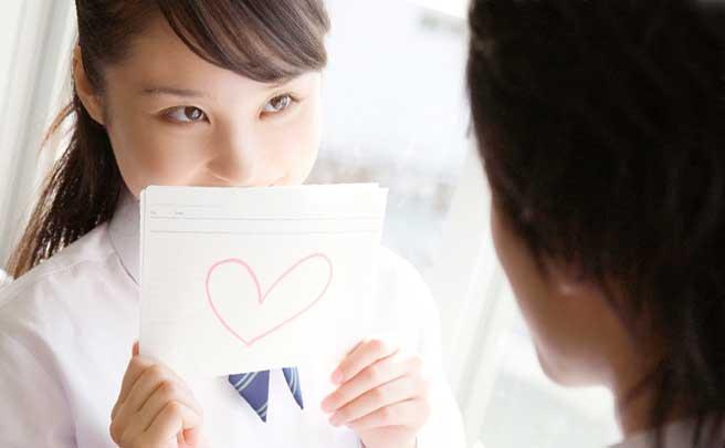 先輩にハートの書いたる紙を恥ずかしそうに見せてる女生徒