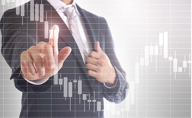 株チャートの変動部分を指差す男性