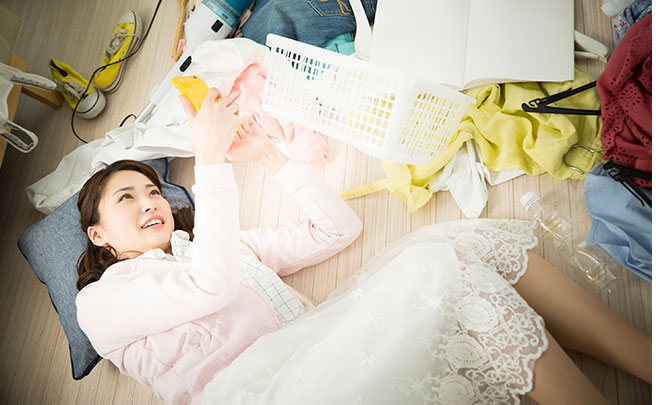 汚い部屋で寝転んでLINEをする女の人