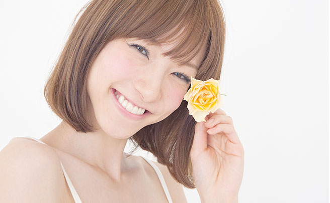 黄色いバラの花を持ってる笑顔の女性