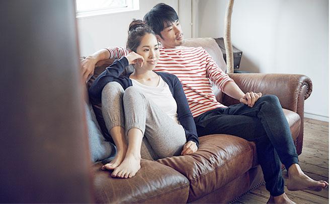 ソファに座ってくつろいでいるカップル