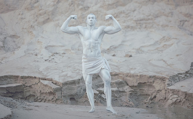 体を白く塗って彫像のようにポーズをとってるムキムキの男性