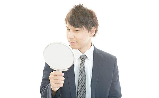 鏡を見て身だしなみを整えている男性