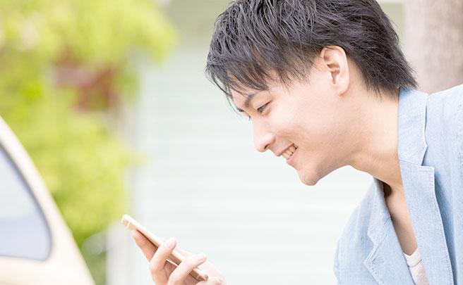 携帯でSNSを見る男性