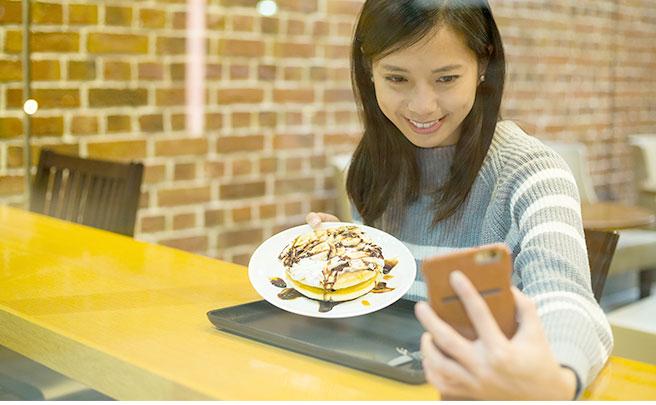 パンケーキを持ってセルフィーを撮る女性