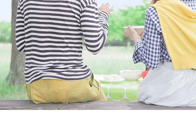 ベンチに座って食事をするカップル