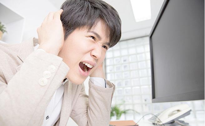 仕事でプレッシャーを感じ頭を抱えている男性