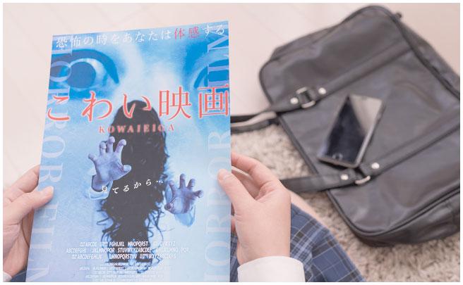 怖い映画の雑誌をみる女子高生の手