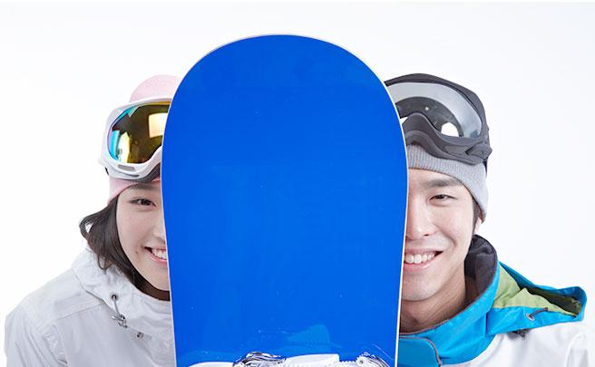 スノーボードの後ろに隠れるカップル