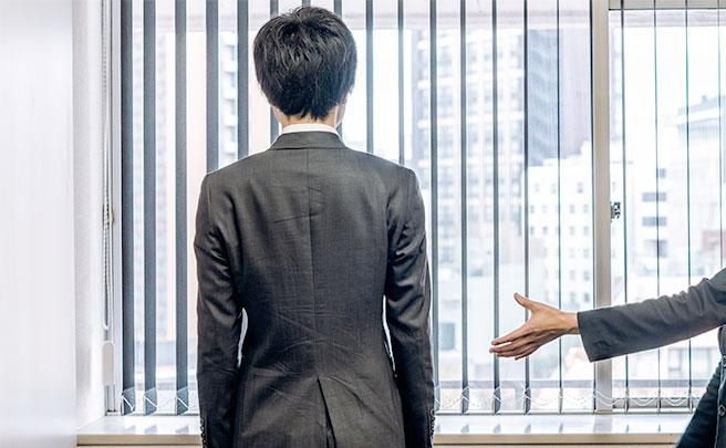 会社で1人外を見てる協調性がない男性