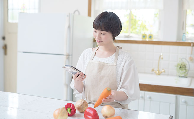 スマホを見ながら料理をする女性