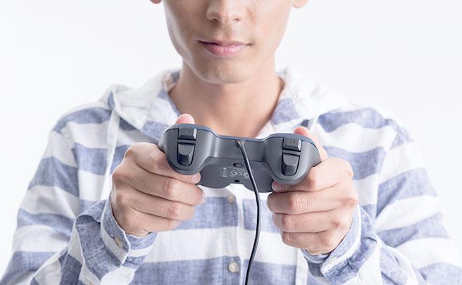 ゲーム機のコントロールを持った男性