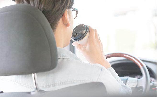 コーヒーを飲みながら運転する男性