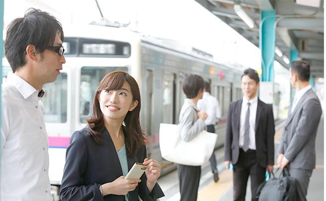 電車乗り場で話す男女
