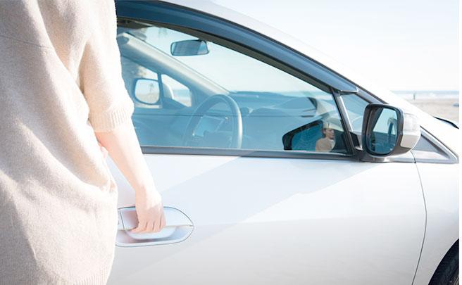 車の運転席に乗る女性