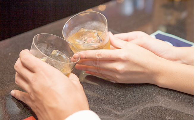 お酒を飲むカップルの手